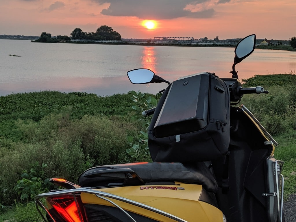 A backpack on a yellow scooter during sunset